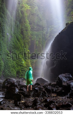 Tourist sees the waterfall in deep forest - stock photo