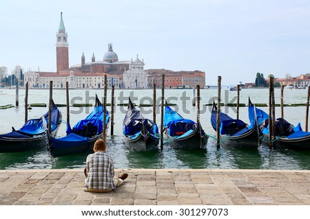 Tourist sitting in San Marco Square in Venice, enjoying the view of Gondolas in Grand Canal  and San Giorgio Maggiore Church in the background ~ Beautiful and relaxing scenery of Venezia Italy  - stock photo