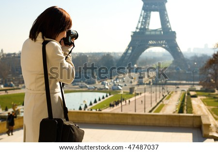 Tourist taking a picture of the Eiffel Tower in Paris - stock photo