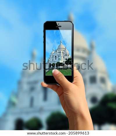 Tourist taking a picture with mobile phone of Basilique du Sacre Coeur - stock photo