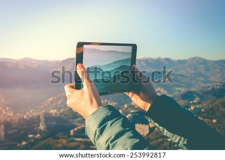 Tourist taking pictures on a tablet in mountains. Toned picture - stock photo