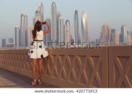 Tourist taking travel picture with phone of Dubai City skyline. Unrecognizable female young adult enjoying UAE vacations in beautiful summer dress. - stock photo