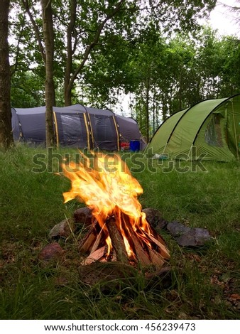 Tourist tents in forest at campsite. Camping tent on nature park in summer. Adventure travel active lifestyle outdoor background. Camping place with armchairs and campfire. Family time holidays. - stock photo