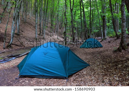 Tourist tents in forest camp near mountain brook - stock photo