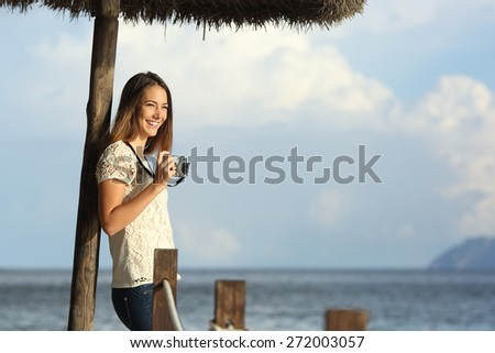 Tourist traveler girl enjoying holidays looking a seascape on the beach holding a vintage slr camera with the sea in the background - stock photo