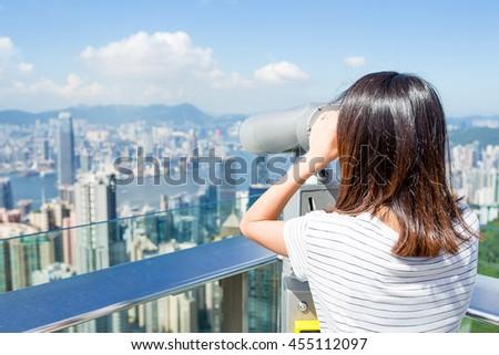 Tourist using binocular looking though Hong Kong cityscape - stock photo