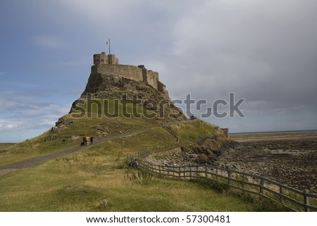 Tourist walk up the path to the Lindisfarne Castle on Holy Island - stock photo
