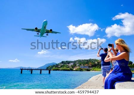 Tourist watching plane landing near Corfu airport. Close landing to the beach - stock photo