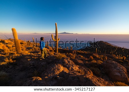 Tourist watching sunrise over the majestic Uyuni Salt Flat, among the most important travel destination in Bolivia. Wide angle from the summit of the Incahuasi Island with glowing rocks and cactus. - stock photo