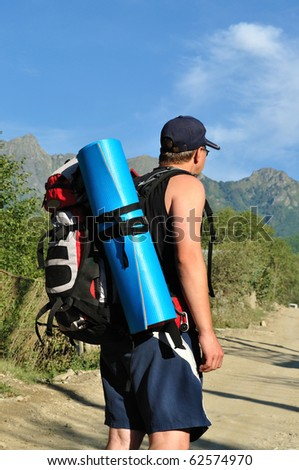 Tourist with a large backpack is a high mountain, on the road, photo from the back - stock photo