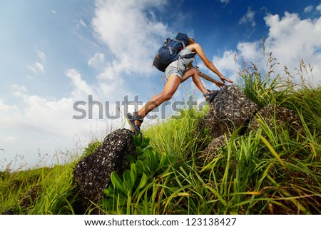 Tourist with backpack crossing rocky terrain with grass at sunny day - stock photo