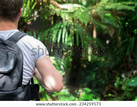 Tourist with backpack in the jungle. Space for your text. - stock photo