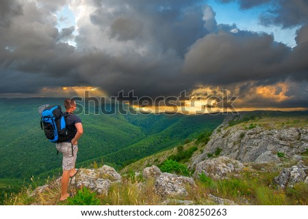 Tourist with backpack standing on a rock and enjoying storm clouds - stock photo