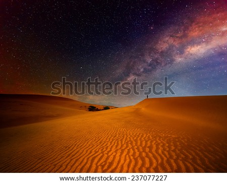 Tourist with backpack standing on top of a mountain and enjoying night sky view with stars. - stock photo