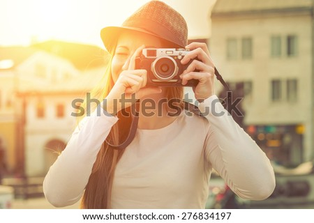Tourist with photo camera shooting on the street - stock photo