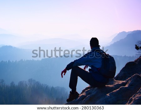 Tourist with sporty backpack sit on rocky peak  and watching into deep misty valley bellow. Sunny spring daybreak in rocky mountains. - stock photo