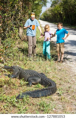 Tourist with two children photographed a large alligator on the phone - stock photo