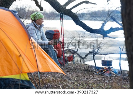 tourist woman sits at the camp in the forest and mountains - stock photo