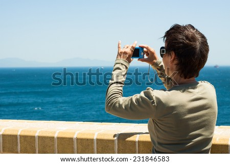Tourist woman taking a picture of blue sea in Gibraltar, UK. - stock photo