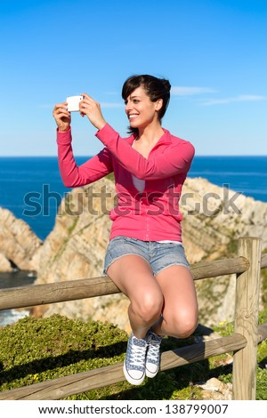 Tourist woman taking photo with cellphone and having fun on summer travel. Joyful brunette girl smiling and taking snapshot with phone on coast landscape. Asturias, Spain. - stock photo