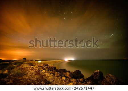 touristic tent on the beach by night - long exposure image - stock photo