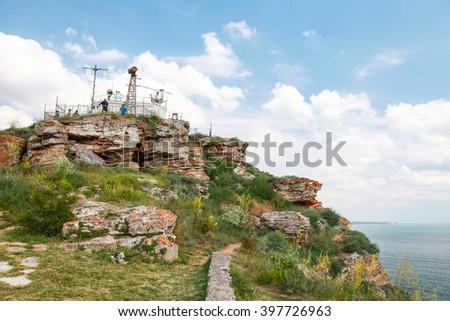 Touristic viewpoint with ordinary tourists on the tip of Kaliakra headland, Bulgaria - stock photo