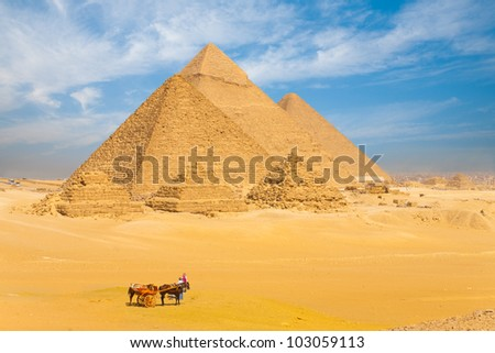 Tourists and transportation donkeys in desert in front of Great Giza pyramids lined up in a row against a beautiful blue sky in Cairo, Egypt. Horizontal copy space - stock photo