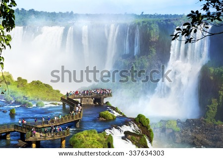 Tourists at Iguazu Falls, one of the world's great natural wonders, on the border of Brazil and Argentina. - stock photo