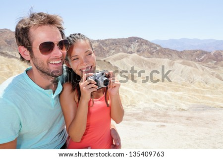 Tourists couple fun in Death Valley. Tourist woman and man taking pictures with camera enjoying the view and desert landscape of Zabriskie Point in Death Valley National Park, California, USA. - stock photo