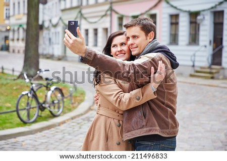 Tourists couple taking photo with smartphone in a city - stock photo