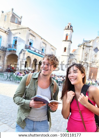 Tourists couple travel having fun smiling happy in Havana, Cuba . Young interracial happy couple on backpacking vacation standing holding reading tourist guide book on Plaza de la Catedral, Old Havana - stock photo