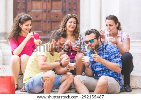 Tourists eating slush, talking and looking each other. The photo was taken in Pisa but could also be used for Rome, Florence or Milan. - stock photo