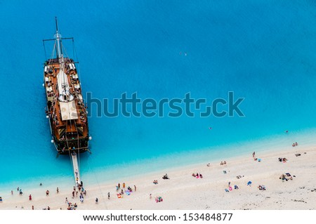 Tourists enjoy swimming in turquoise clear waters of hidden beach as a part of a historic cruise - stock photo