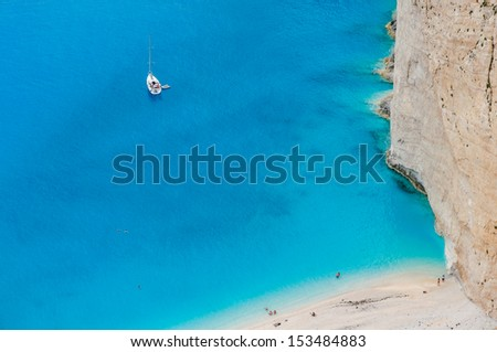 Tourists enjoy swimming in turquoise clear waters of hidden beach as a part of a private yacht cruise - stock photo
