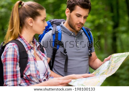 Tourists examining map. Thoughtful young couple with backpacks examining map while standing in nature - stock photo