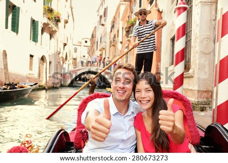 Tourists happy couple traveling in Venice gondola giving thumbs up hand sign joyful on travel. Romantic young beautiful couple on vacation holidays sailing in venetian canal in gondole. Italy - stock photo