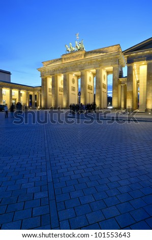 tourists in front of brandenburg gate in berlin, germany, at night - stock photo