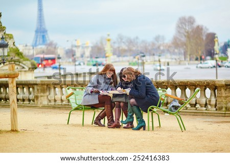 Tourists in Paris planning their trip using map - stock photo
