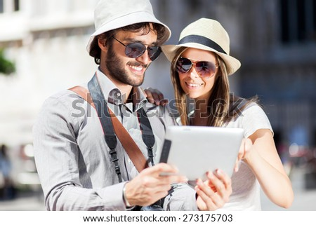 Tourists looking at the tablet - stock photo