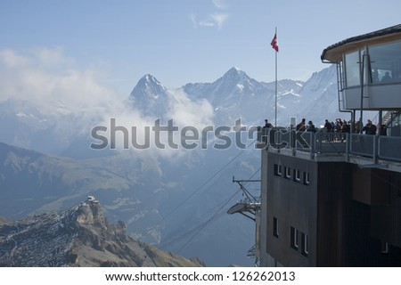 Tourists observe the Swiss Alps from Schilthorn, Switzerland - stock photo