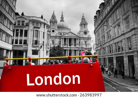 Tourists on a London Sightseeing bus, St Paul's Cathedral in the distance. - stock photo