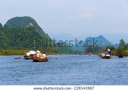 Tourists on the boat in Yen stream to HUONG Pagoda. HUONG Pagoda is a famous heritage place in Hanoi, Vietnam. - stock photo