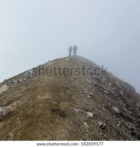 Tourists on the crater of the volcano Gorely in a fog - Kamchatka, Russia - stock photo