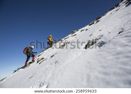 Tourists reaches the top of a snowy mountain at sunny winter day. - stock photo