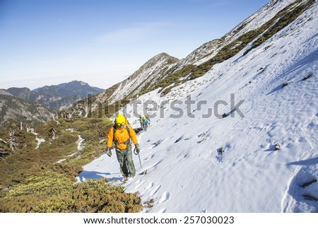 Tourists reaches the top of a snowy mountain in a sunny winter day. - stock photo