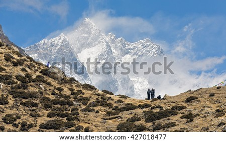 Tourists rest on the pass above the village of Dingboche. In the background is one of the highest peaks of the World Lhotse (8516 m) - Nepal, Himalayas - stock photo