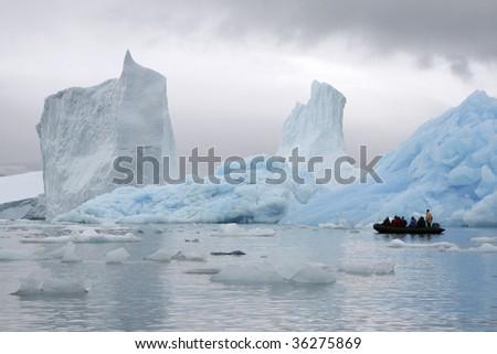 Tourists sailing between huge icebergs in Napassorsuaq Fjord, Greenland - stock photo