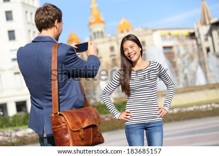 Tourists taking picture on travel in Barcelona. Happy urban young couple taking photo portrait with smart phone camera. Man and woman on Placa de Catalunya, Catalonia Square, Barcelona, Spain. - stock photo
