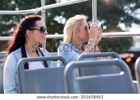 tourists taking pictures from an open top bus while touring the city - stock photo