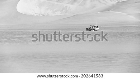 Tourists travel through the dunes in the Atacama Desert - Oasis of Huacachina, Peru, South America (black and white) - stock photo